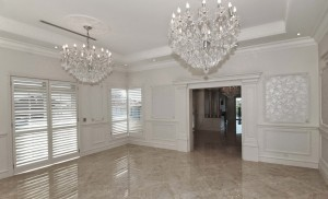 The marble floors give each room an air of stamped elegance. In this conversational room the cachet is added by the in-framed wallpapered walls.